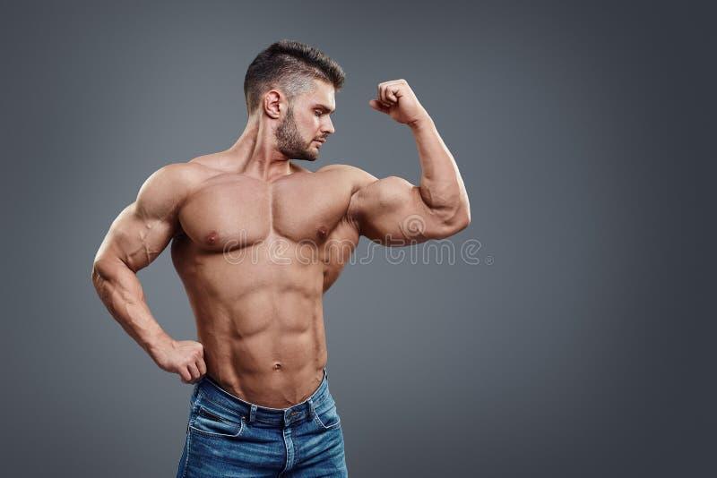 Bodybuilder het stellen op grijze achtergrond royalty-vrije stock afbeeldingen