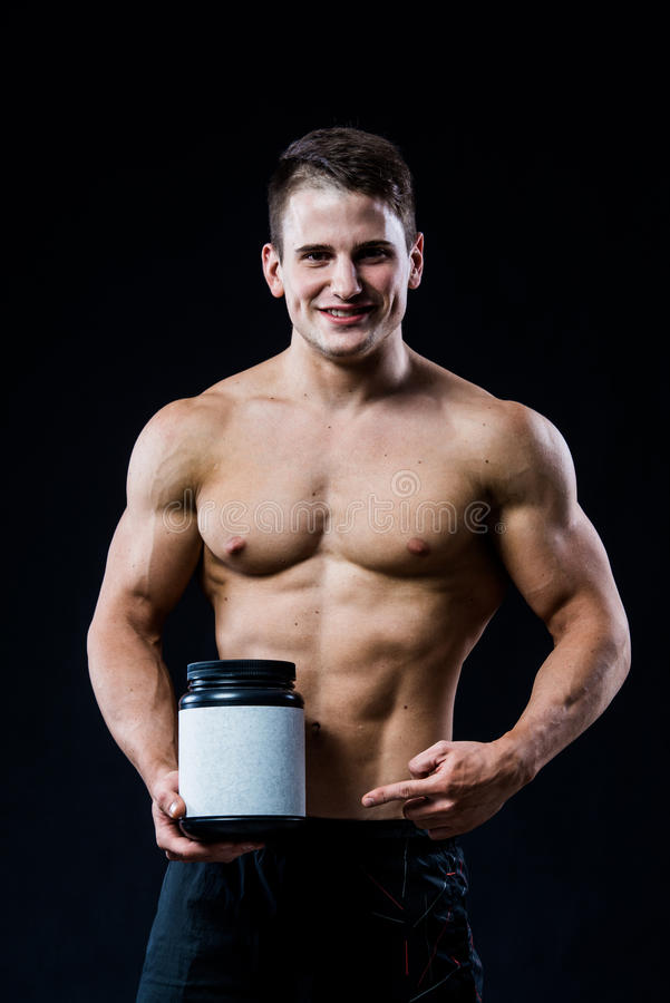 Bodybuilder holding a black plastic jar blank white label whey protein and pointing to it with his hand isolated on dark royalty free stock photography