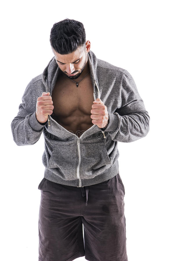 Bodybuilder looking inside his shirt, checking out his muscles royalty free stock photography