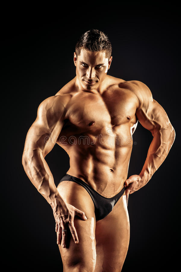 Bodybuilder man. Handsome muscular bodybuilder posing over black background stock photos