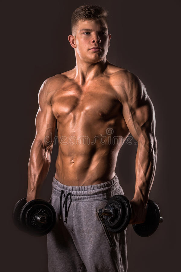 Bodybuilder man posing with dumbbells royalty free stock photography
