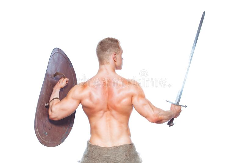 Bodybuilder man posing with a sword and shield isolated on white background. Serious shirtless man demonstrating his royalty free stock photo