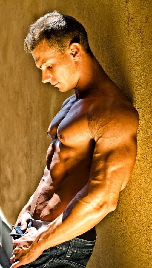 Bodybuilder masculin musculaire beau se penchant contre le mur jaune image libre de droits