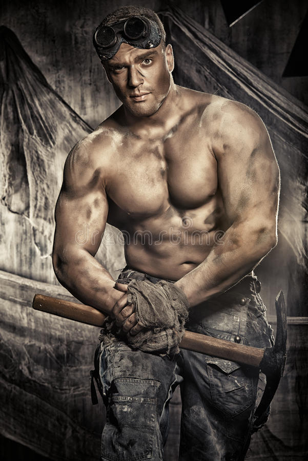 Bodybuilder. Masculine dirty coal miner with a pickaxe over dark grunge background. Mining industry. Strength. Bodybuilding stock image