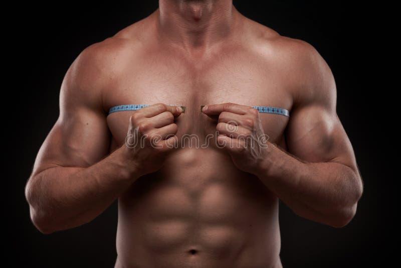 Bodybuilder met een metende band rond zijn borst stock foto's