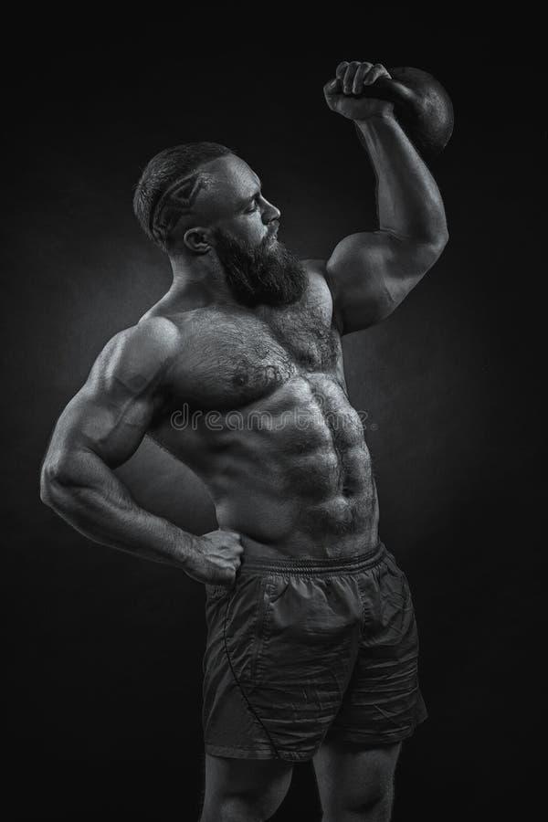 Bodybuilder mit einem Bart hebt ein schweres kettlebell an stockbild