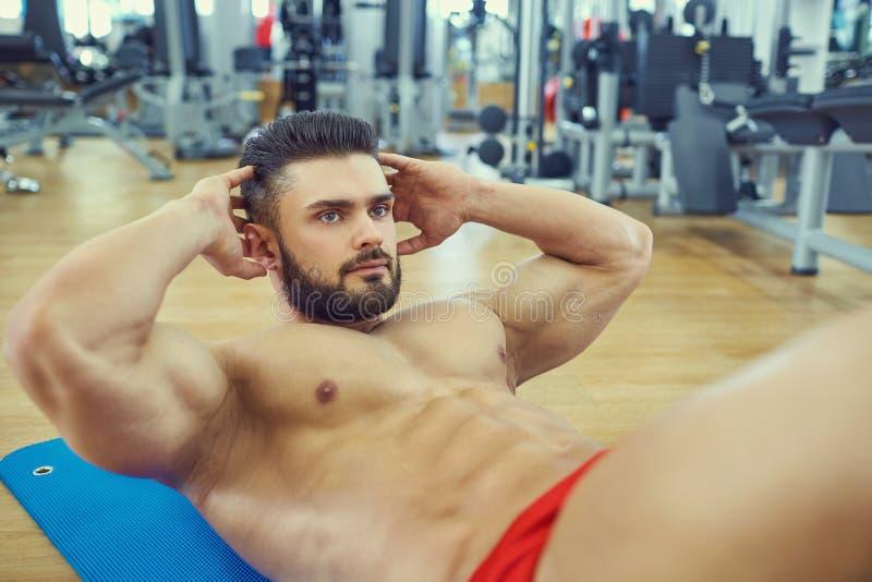 Bodybuilder mit einem Bart tut ABSübung auf dem Boden im g stockbilder