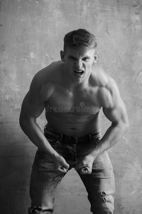 Bodybuilder montrant des muscles sur le torse fort et nu photographie stock