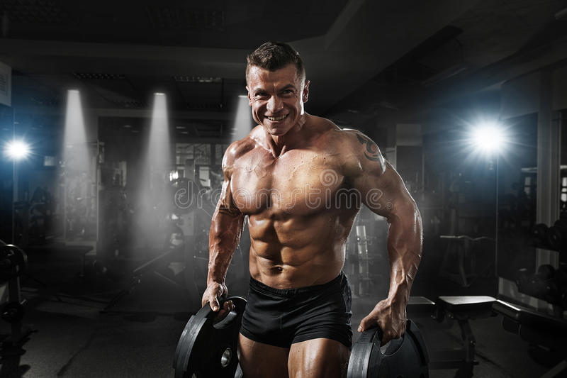 Bodybuilder muscle Athlete training with weight in gym. Bodybuilder muscle smiling Athlete training with weight in gym royalty free stock photo