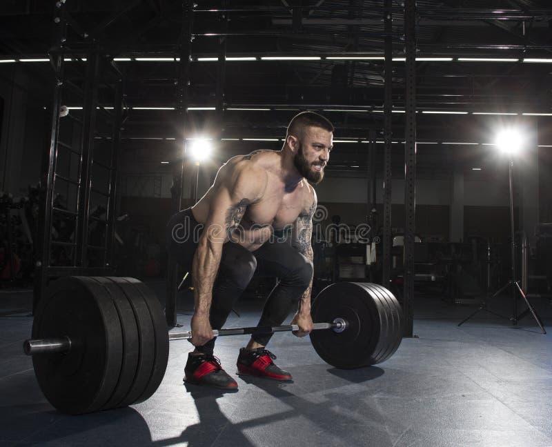 Bodybuilder musculaire attirant faisant l'exercice lourd de deadlift dedans photographie stock libre de droits