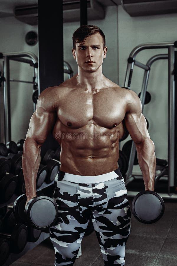 Bodybuilder musculaire fort faisant l'exercice dans le gymnase Une partie de corps de forme physique photographie stock