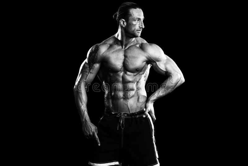 Bodybuilder musculaire Guy Posing Over Black Background photos stock