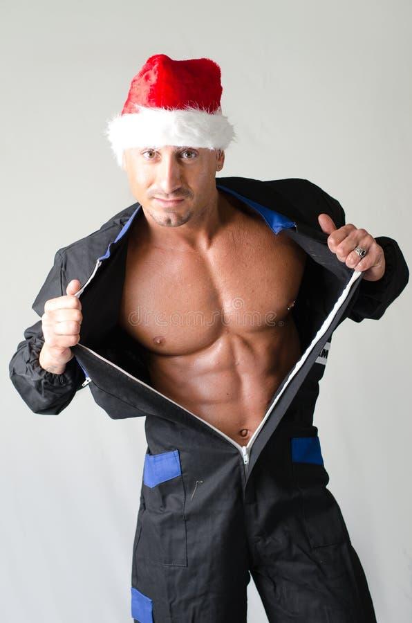 Bodybuilder musculaire utilisant le chapeau de rouge de Santa Claus image stock