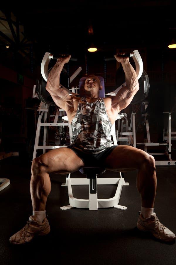 Bodybuilder no quarto do treinamento imagens de stock