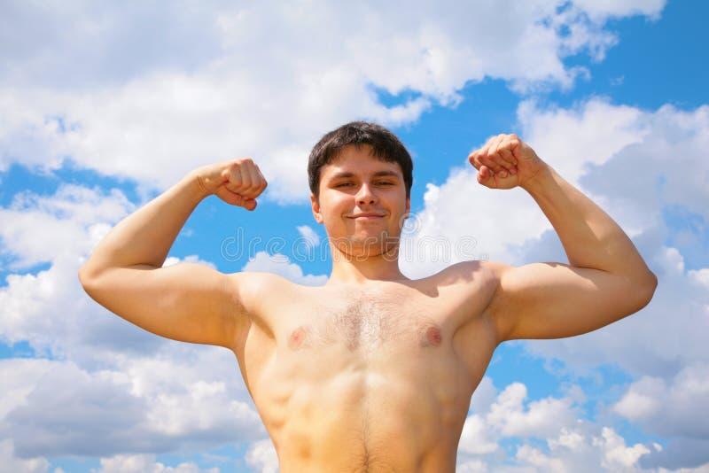 Bodybuilder op hemelachtergrond royalty-vrije stock afbeelding