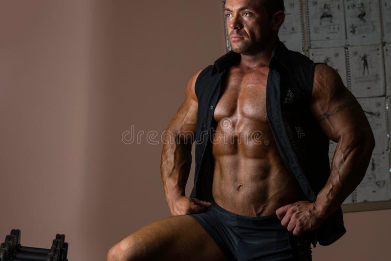 Bodybuilder posant dans la chemise noire sans douilles photos stock