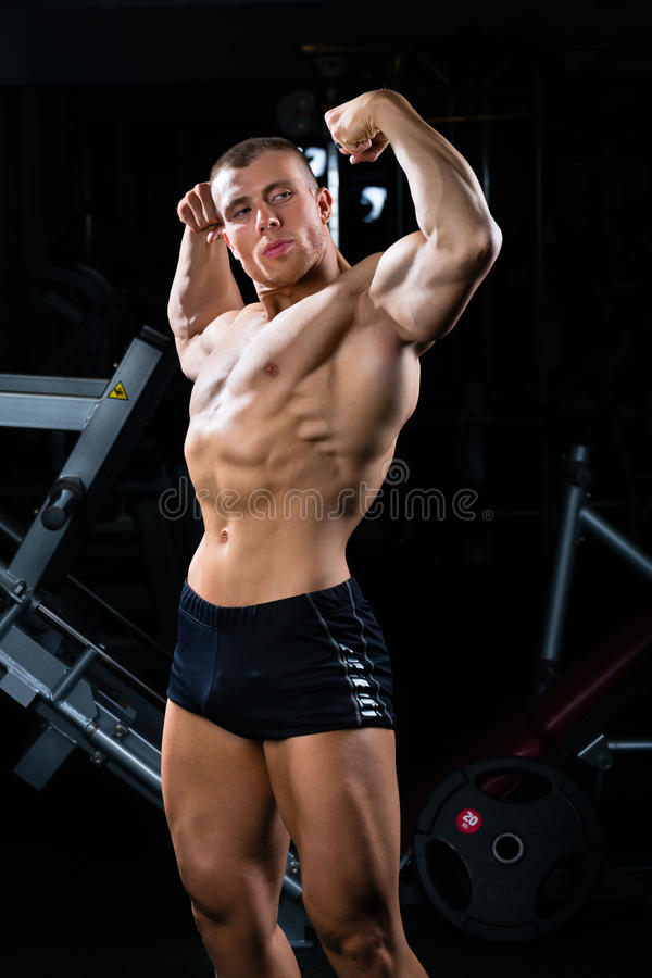 Bodybuilder posant dans le gymnase photos libres de droits