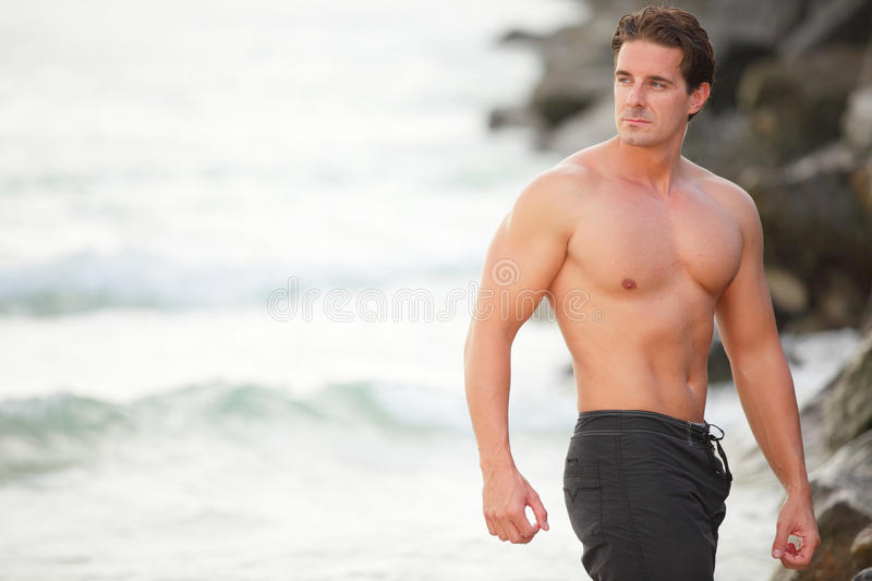 Bodybuilder posing on the beach stock image