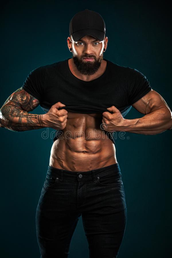 Strong and fit man bodybuilder. Sporty muscular guy athlete. Sport and fitness concept. Men`s fashion. stock photo