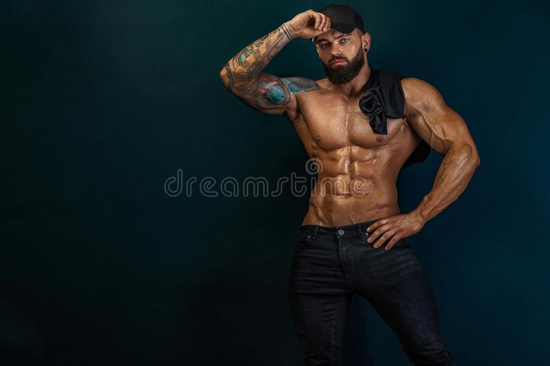 Strong and fit man bodybuilder. Sporty muscular guy athlete. Sport and fitness concept. Men`s fashion. royalty free stock photo