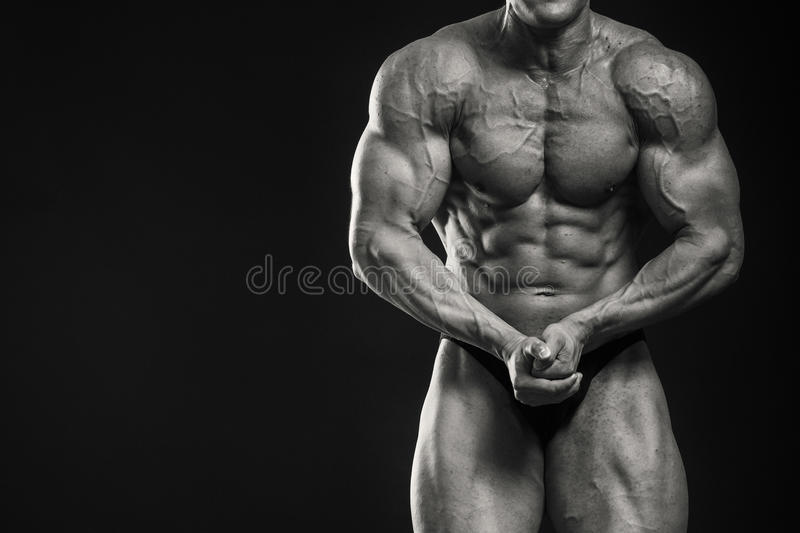 Bodybuilder. Posing on a black background. Muscular man showing his muscules stock photo