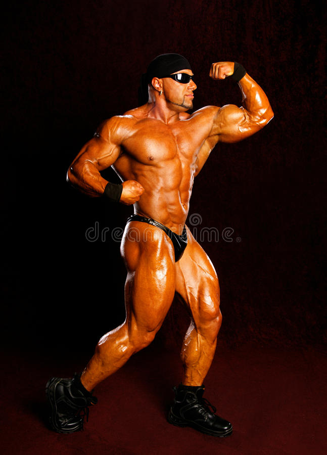 Bodybuilder. Posing on a dark background royalty free stock image