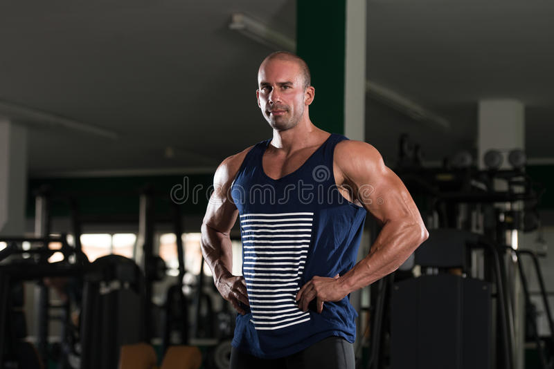Bodybuilder Posing In The Gym. Young Bald Man Standing Strong In The Gym And Flexing Muscles - Muscular Athletic Bodybuilder Fitness Model Posing After Exercises stock image