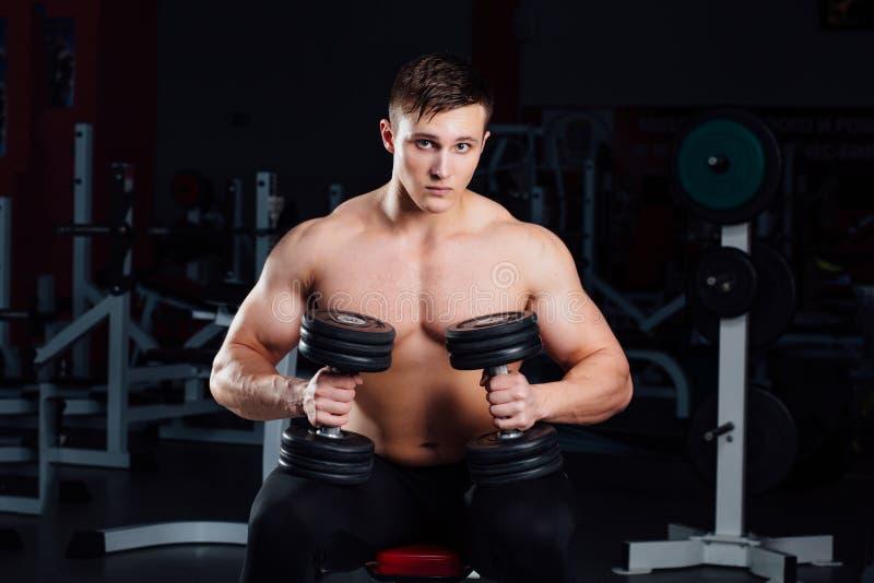 Bodybuilder professionnel s'asseyant sur le banc, se reposant entre les exercices avec des haltères au gymnase grand image stock