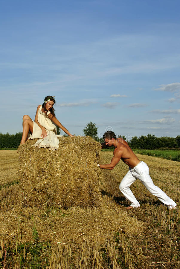 Bodybuilder Pushes A Haystack With A Girl On Top Royalty Free Stock Images