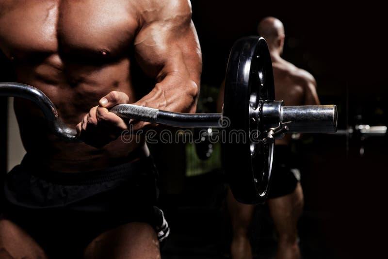 Bodybuilder com o Barbell na frente da baixa chave do espelho fotografia de stock