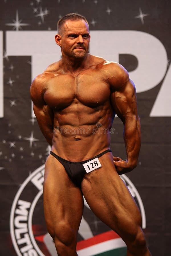 Bodybuilder que flexiona seus músculos imagens de stock royalty free