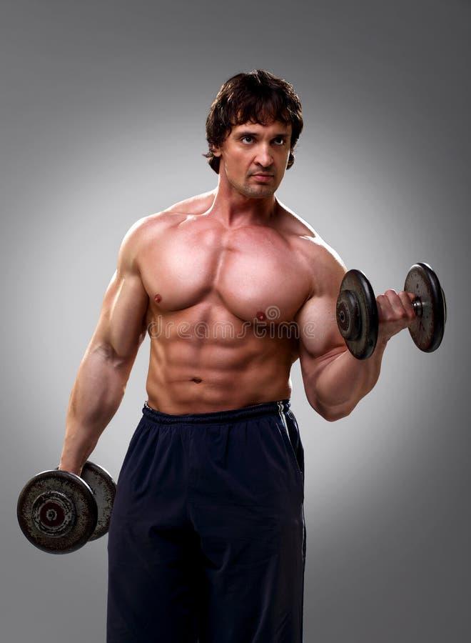 Bodybuilder que hace su bíceps fotografía de archivo