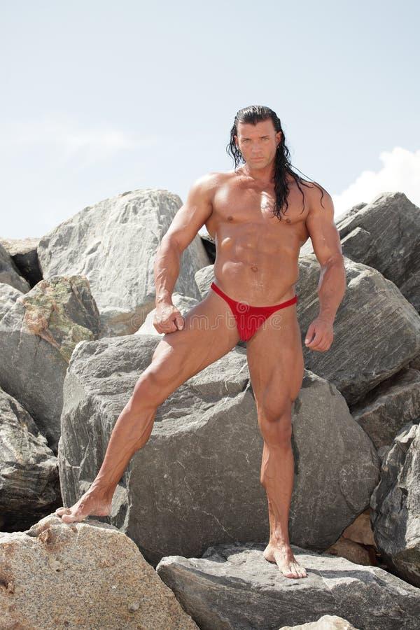 Bodybuilder que presenta en las rocas imágenes de archivo libres de regalías