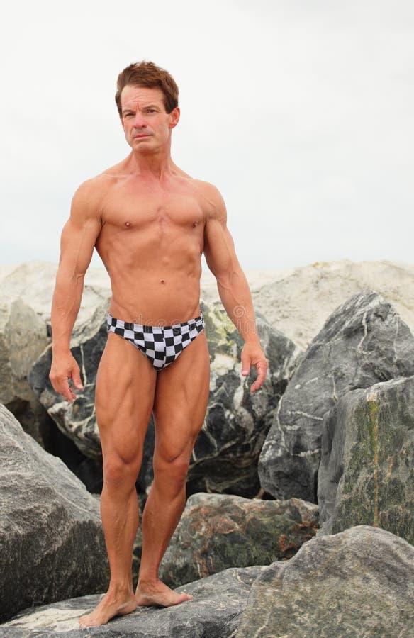 Bodybuilder que presenta en speedos foto de archivo libre de regalías