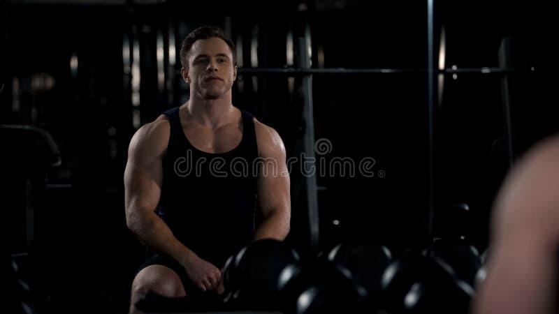 Bodybuilder regardant se dans le miroir après la séance d'entraînement, satisfaite des résultats photographie stock