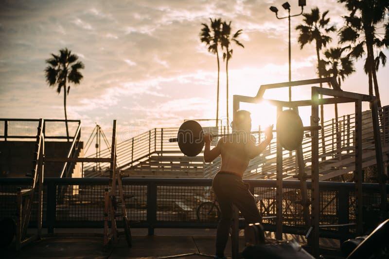Bodybuilder s'exerçant au coucher du soleil photographie stock