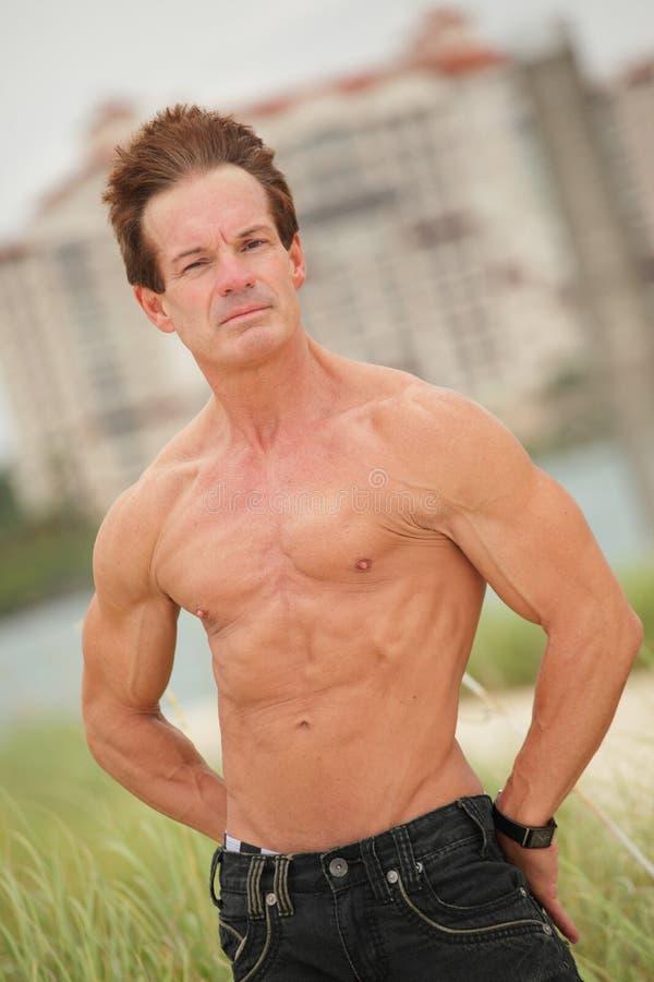 Bodybuilder senza camicia sulla spiaggia fotografie stock libere da diritti