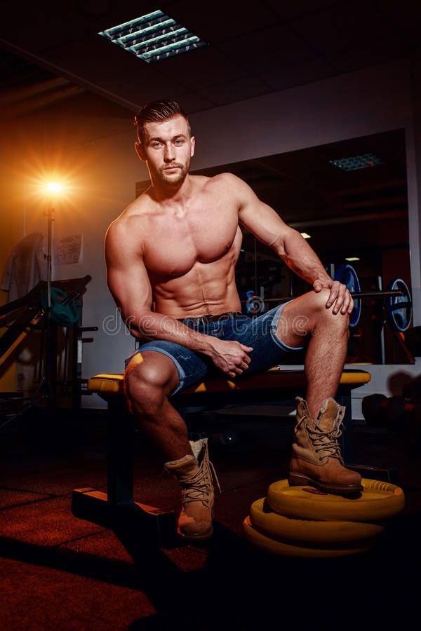 Bodybuilder sits on a weight bench, he takes a break. Muscular man at a workout place in a gym and smiling to camera. stock image