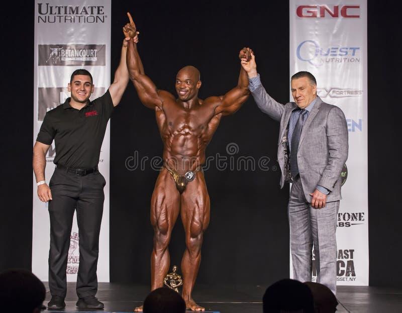 Bodybuilder soulevant des bras dans la victoire image libre de droits