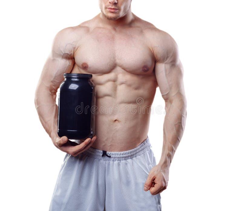 Bodybuilder tenant un pot en plastique noir avec de la protéine de lactalbumine sur le fond blanc Aucun visage photographie stock libre de droits
