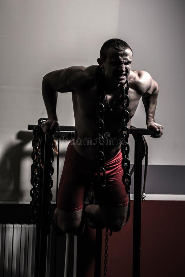 Bodybuilder w gym wykonuje ćwiczenia dla bodybuilding zdjęcia stock