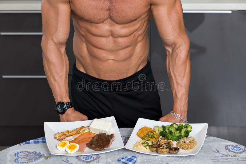 Bodybuilder w kuchni; zwierzę versus rośliien proteiny obraz stock