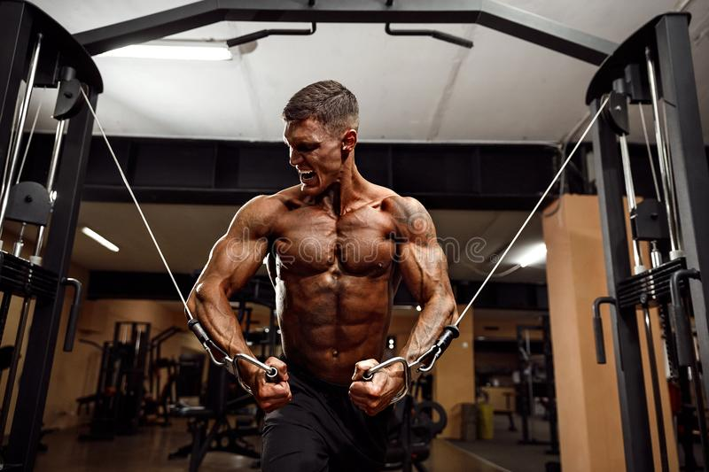 Bodybuilder Is Working On His Chest With Cable Crossover In Gym. Scream for motivation royalty free stock photo