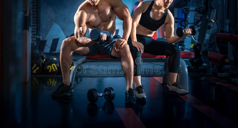 Bodybuilder working out with dumbbell weights at the gym. Young couple is working out at gym. Attractive woman and handsome royalty free stock images