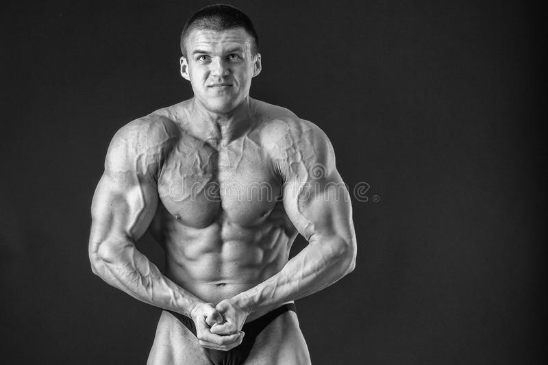 Bodybuilder. Young bodybuilder guy in good shape against a dark background. Man posing, showing his muscle definition. A man shows his tense muscles. Strength royalty free stock photos