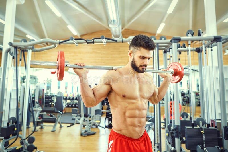 Bodybuilder z prętowym barbell robi ćwiczeniom w gym obraz stock