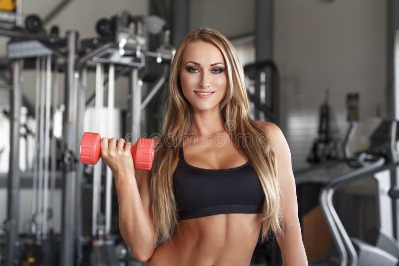 Bodybuilderfrau mit bunten Dummköpfen stockbilder