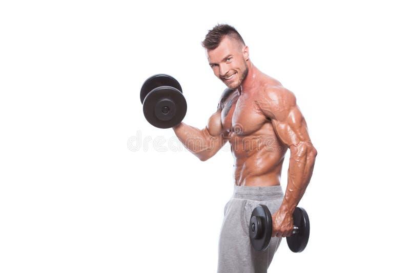 Bodybuilderkerl, der Übungen mit Dummköpfen tut lizenzfreie stockfotos