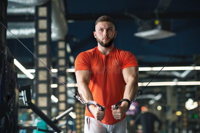 Bodybuilderkerl in der Turnhalle, die oben nah H?nde oben pumpt lizenzfreie stockbilder