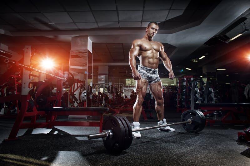 Bodybuildermann, der mit Barbell, Training in der Turnhalle steht stockbilder